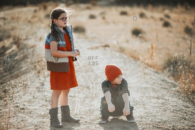 Boy and girl in color-coordinated outfits on dirt road
