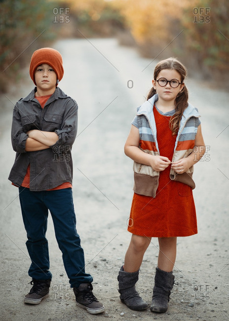 Young siblings on dirt road in color-coordinated outfits