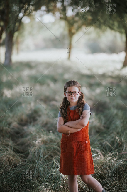Girl in round glasses and orange dress stands with arms crossed