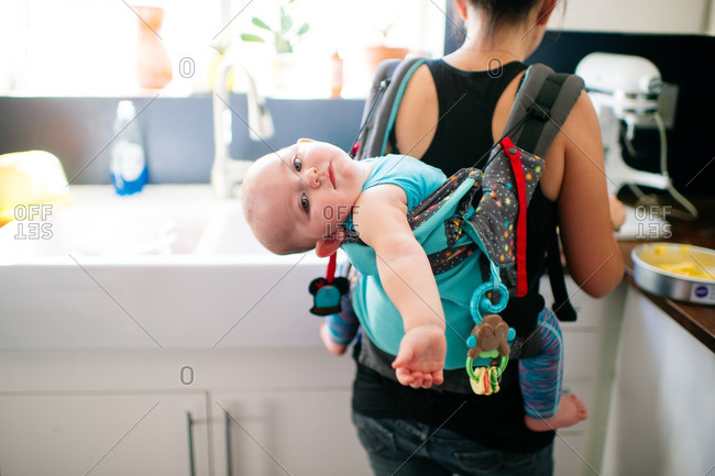 Baby leaning out of mother's backpack carrier