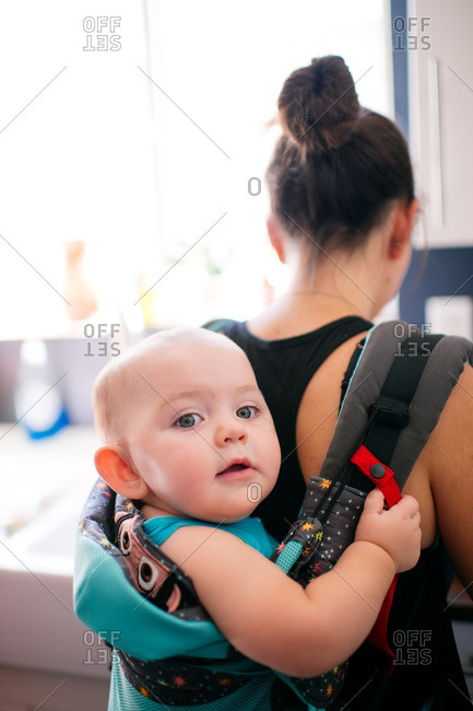 Content baby in mother's backpack carrier