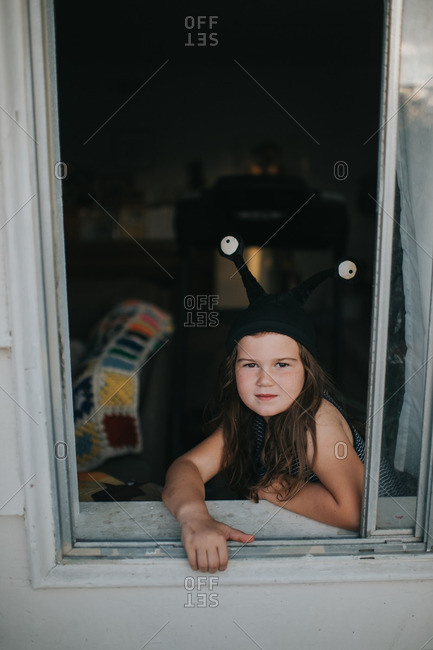 Cute young girl wearing alien hat looks through window