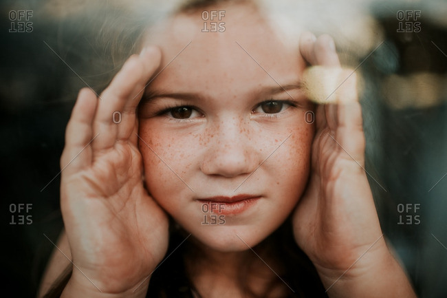 Girl with brown eyes and freckles with her hands up against glass window
