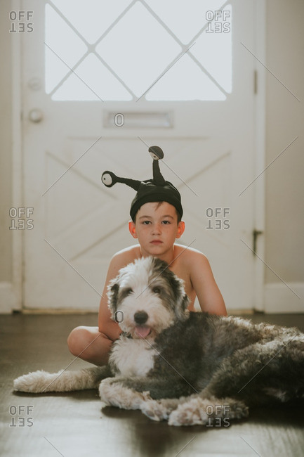Portrait of a boy in alien hat sitting with his dog