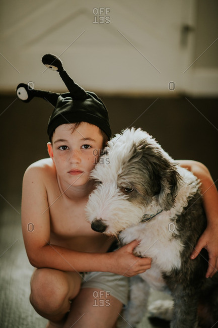 Boy in an alien hat hugging his dog