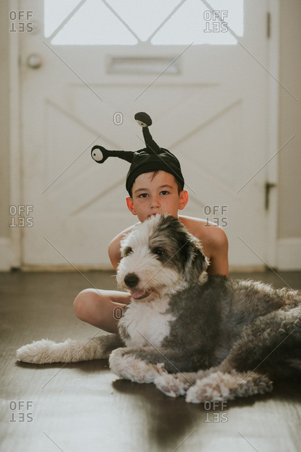 Boy in an alien hat hiding behind his dog