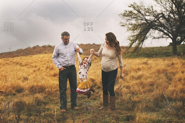 Parents lifting girl in rural setting