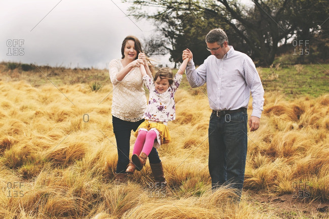 Parents swinging a girl in field