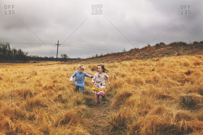 Boy and girl running down a field