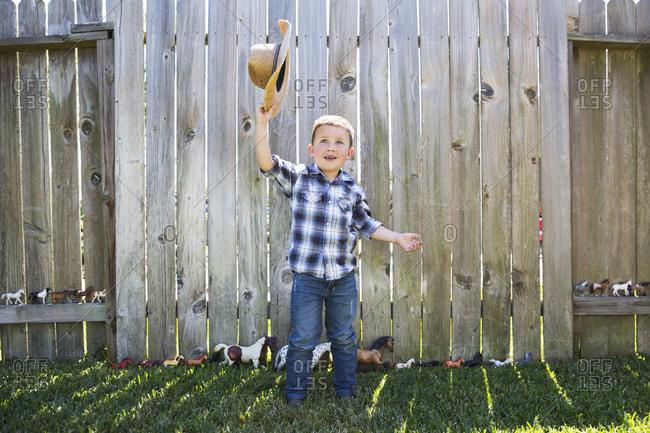 Caucasian boy waving cowboy hat