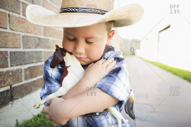 Caucasian boy wearing cowboy hat hugging toy horse