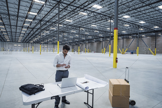 Indian architect texting on cell phone in empty warehouse