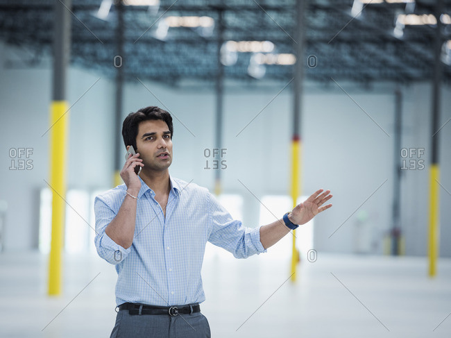Indian businessman talking on cell phone in empty warehouse