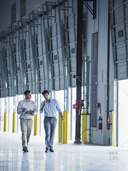 Businessmen walking with clipboard near open loading dock doors