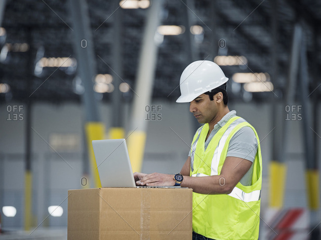 Indian worker using laptop on cardboard box in warehouse