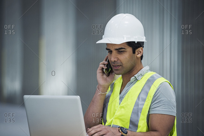 Indian worker using laptop and cell phone in warehouse