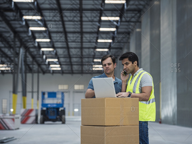 Workers using laptop and cell phone in warehouse