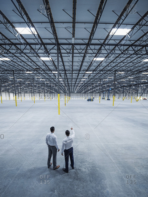 Businessmen talking in empty warehouse