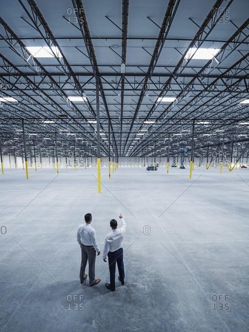 Businessmen talking in empty warehouse