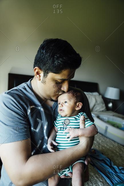 Hispanic man kissing forehead of baby boy