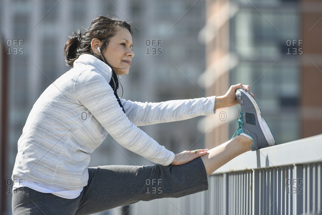 Hispanic woman stretching leg in city