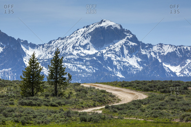 Winding dirt road near snow covered mountain range