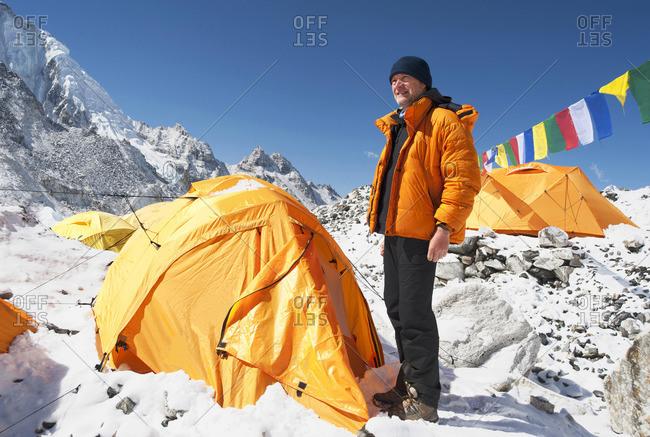 Man standing at base camp tent, Everest, Khumbu region, Nepal