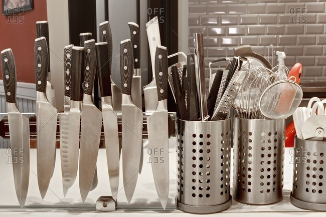 Knives on magnetic rack in commercial kitchen