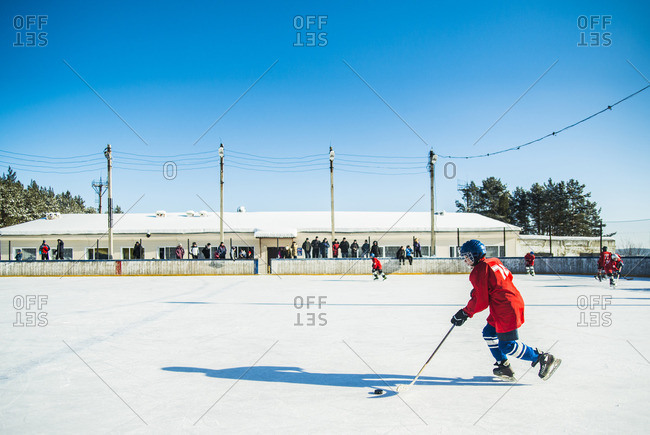 Caucasian boys playing ice hockey outdoors