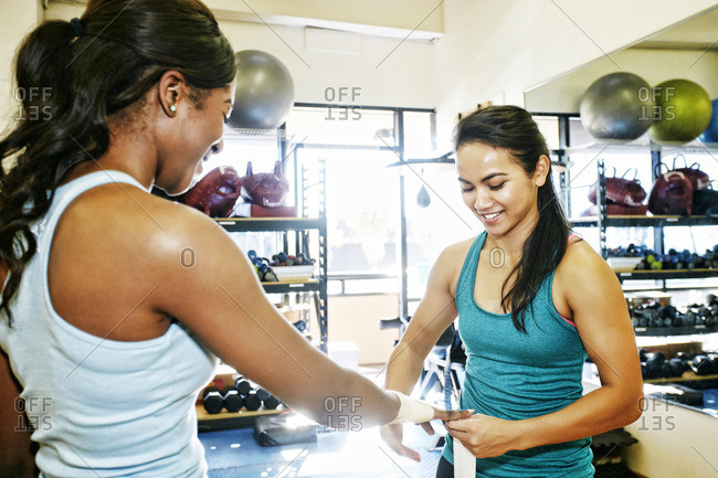 Woman wrapping hands of friend in gymnasium