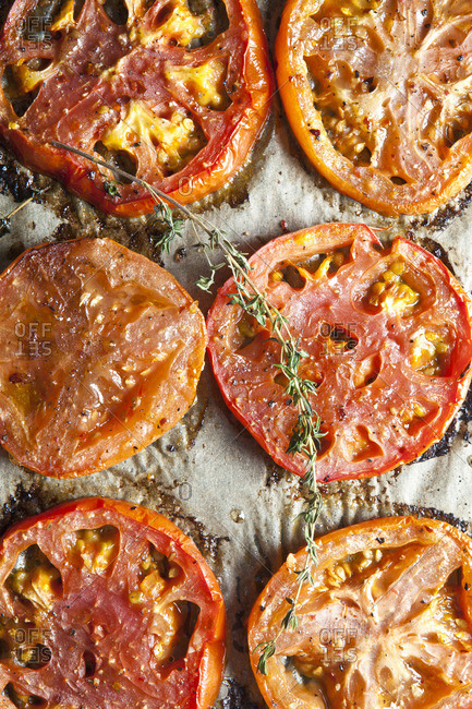 Slices of roasted tomatoes with herbs