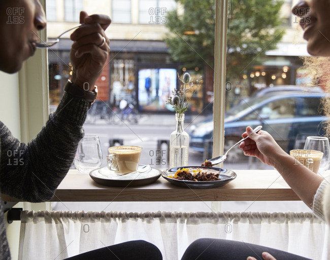 Close up of couple enjoying chocolate brownie in cafe