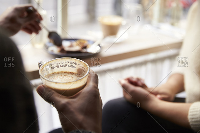 Close up of couple enjoying coffee and cake in cafe