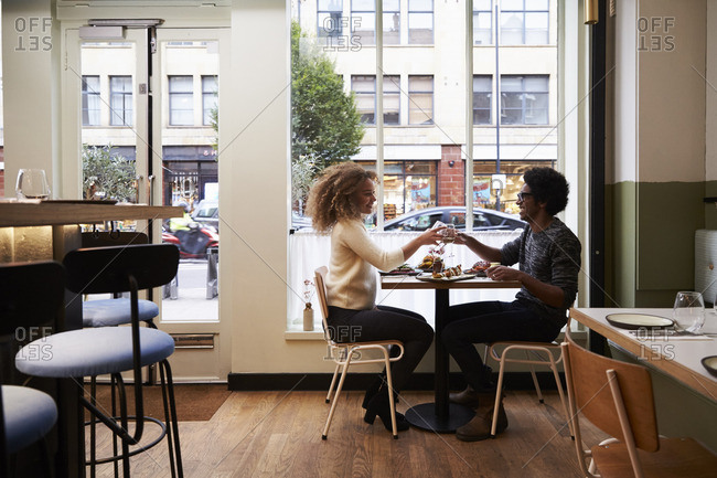 Young couple making toast on date in city restaurant