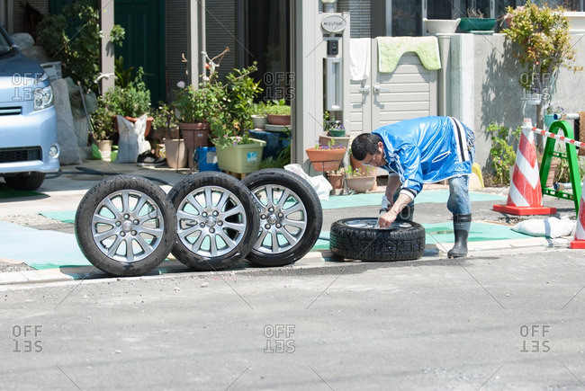 Tokyo, Japan - April 24, 2011: Man washing automobile tires