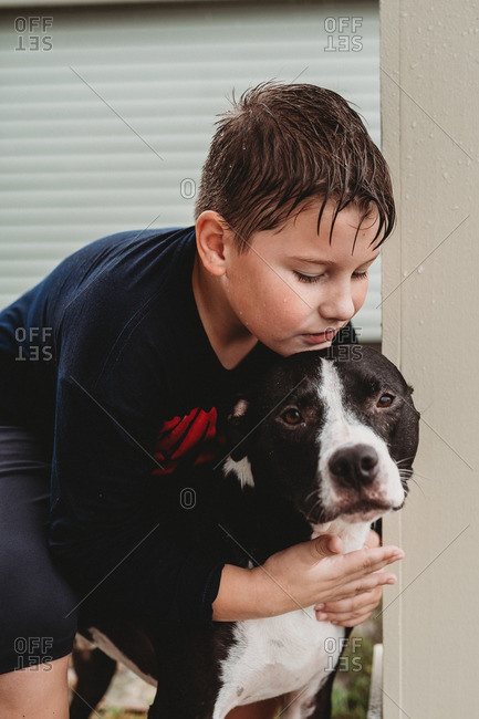 Boy playing outside in the rain with his dog