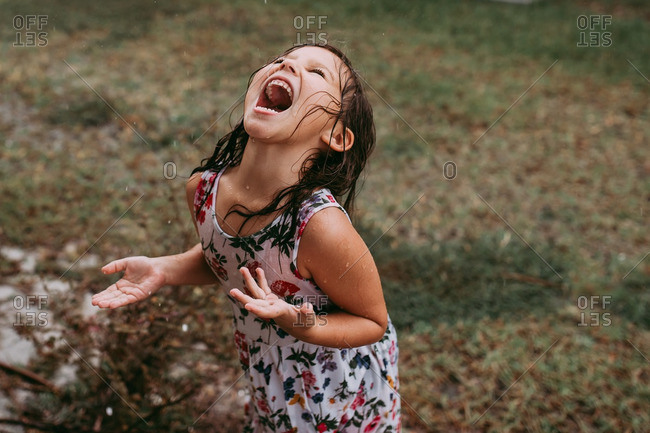 Young girl standing in the rain catching raindrops