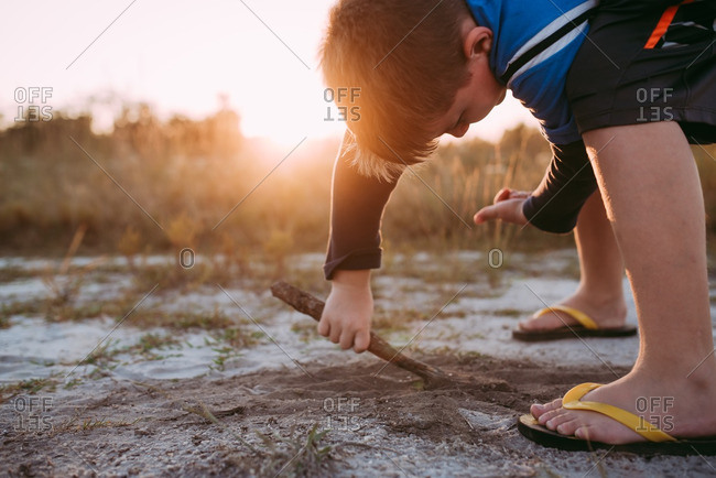 Boy drawing in the sand with a stick at sunset