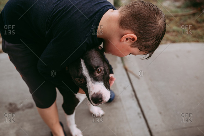 Boy hugging his dog while playing in the rain