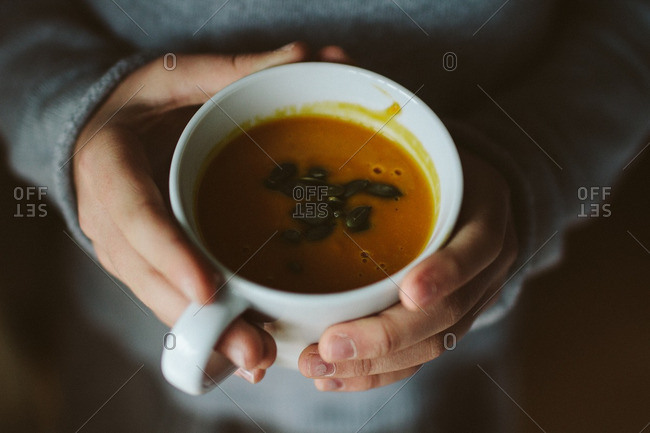 Hands holding a cup of pumpkin soup