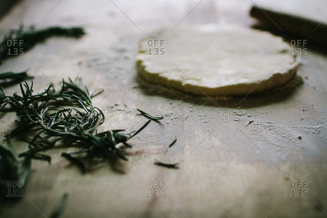 Flattened cookie dough and fresh rosemary