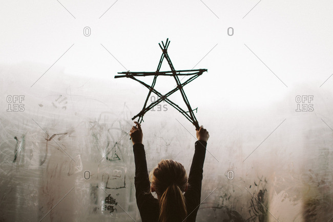 Girl holding star made from twigs