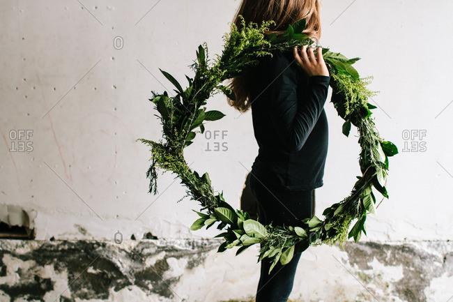 Girl carrying green wreath