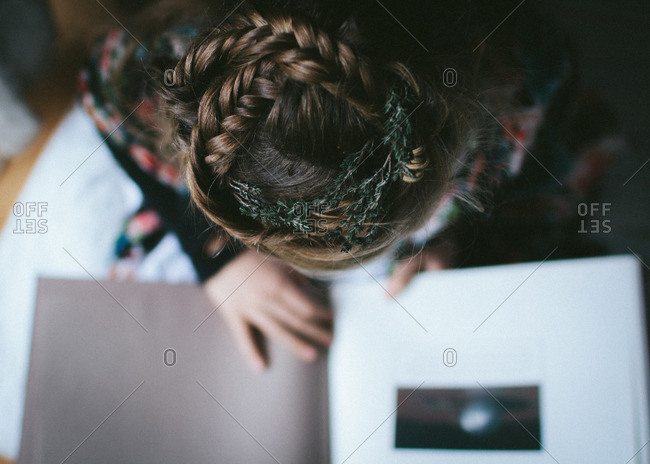 Little girl reading a book with thyme in her hair