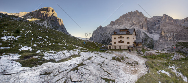 Trentino Alto Adige, Italy - August 27, 2016: The alpine refuge Zsigmondy-Comici with Cima Undici behind illuminated at sunset, Bolzano district, South Tyrol