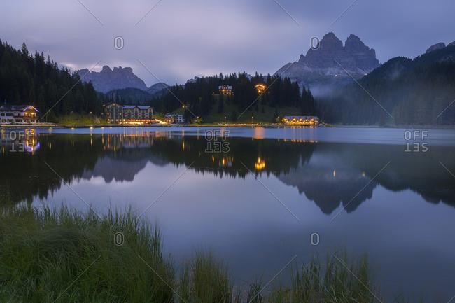 The evening lights illuminate the Lake Misurina with the Tre cime of Lavaredo in the background, Belluno, Veneto, Italy