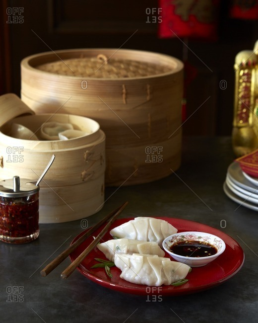 Chinese dumplings served on a red plate with chopsticks, soy sauce, and chili oil