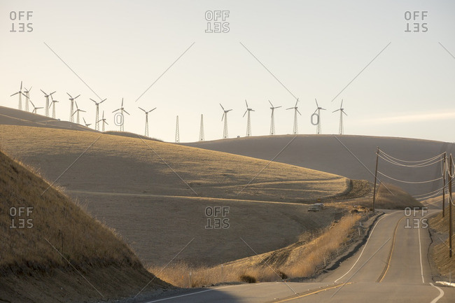 Wind turbines on hills beside a remote highway