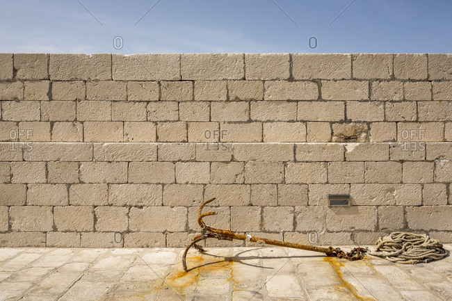 Rusted anchor and rope beside a stone wall