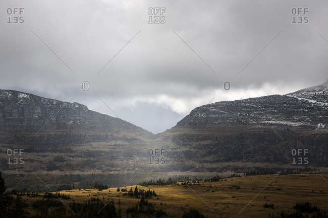 Distant mountains and rolling hills under storm clouds in Glacier National Park